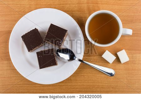 Cakes With Chocolate In Plate, Lumpy Sugar, Tea And Teaspoon