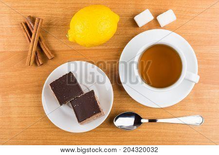 Cakes With Chocolate In Saucer, Cinnamon Sticks, Lemon, Sugar, Tea