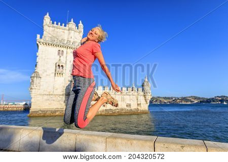 Happy blonde caucasian woman jumping at Belem Tower, Unesco Heritage and symbol of Lisbon, in Belem District, Tagus River. Lifestyle traveler female enjoying Torre de Belem. Freedom and travel concept