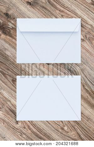 Blank white envelopes on wooden background, two sides. Template for your design. Mockup object