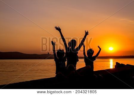 Silhouettes of mother and kids at sunset