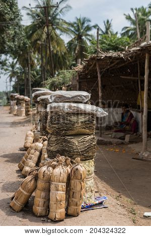 Mysore India - October 27 2013: In downtown Bannur village stacks of dried banana and saal tree leaves stand in front of dilapidated workshops where women fold and stitch cups and plates with them.