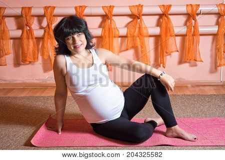 Pregnancy Yoga and Fitness concept. Healthy maternity lifestyle concept. 40 week pregnant middle aged caucasian woman sitting with positive smile while rest on the mat during sport exersises.