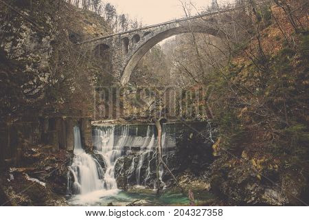 Waterfall from stone dam flow to green pool with white foaming under brick bridge sidewalk in autumn forest with yellow orange green leaves trees, Clear water river through barrage to emerald pond surrounding by rock cliff covered in trees and wood under