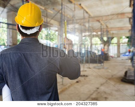 Engineer with tape measure in building construction site