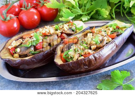 Eggplants stuffed with mushrooms onions carrots tomatoes and nuts on a metal plate on a grey background. Vegetarian food. healthy eating concept