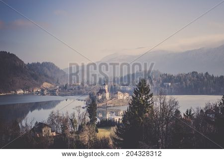 The Lake Bled lies in picturesque environment surrounded by hills and forest with medieval castle stands and several buildings on small island, Gorgeous view of Bled castle reflect on Lake Bled in the Julian alps seen from Little Osojnica Hill with many g