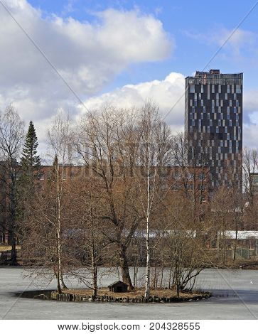 frozen pond and tall building in Tampere, Finland