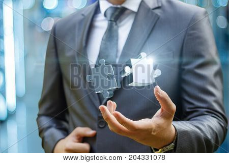 Businessman Showing Two Of The Puzzle In Hand.