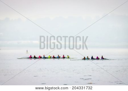 A foggy morning on the Potomac River compete with scullers in color clothing.