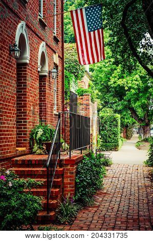 A flag flying over a Virginia street with cobblestone sidewalks and historic red brick houses.