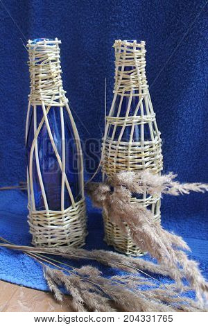two glass fragile blue bottle weaved willow stay on blue background for new wine