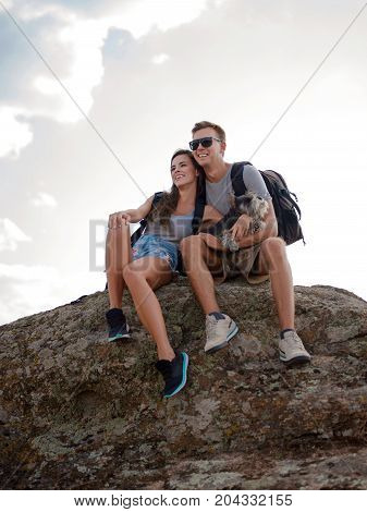 Hikers and their pet with backpacks relaxing on top of a hill and enjoying view of sunset in canyoun.