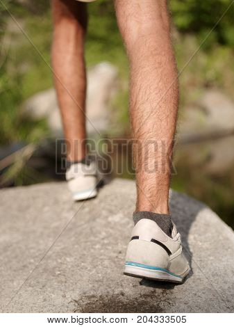 close-up photo of foots at the natural view. Climbing the rock. Sport and active life concept.