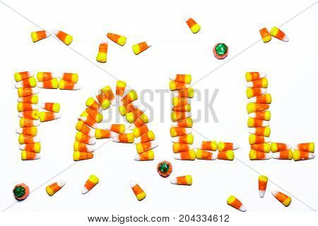 The word FALL is spelled using tri-colored candy corn candy on a white back ground