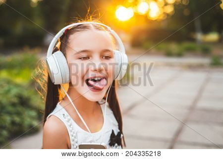 funny girl with headphones showing tongue, sweet teenager in white headphones at sunset, child and hi-tech concept