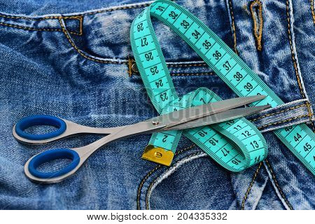 Making clothes and design concept. Tailors tools on denim textile. Jeans belt loops zipper and pocket close up selective focus. Metal scissors and blue measure tape on jeans.