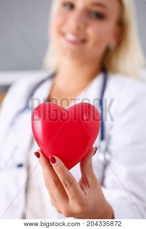 Smiling Female Doctor Hold In Arms Red Heart