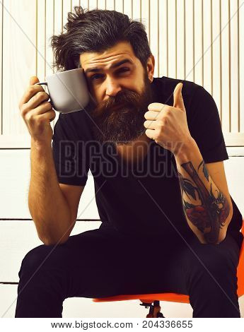 Bearded man long beard. Brutal tattooed smiling caucasian hipster with moustache holding cup or mug in rock black style sitting on acid orange chair on white wooden vintage studio background
