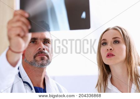Mature Male Doctor Hold In Arm And Look At Xray Photography