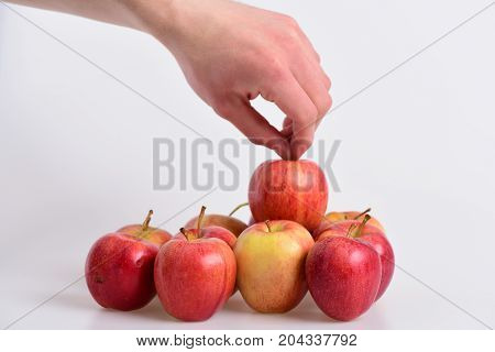 Male Hand Holds Light Red Apple Above Other Fruits.