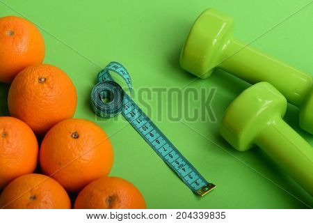 Oranges Near Dumbbells, Measuring Tape On Green Background