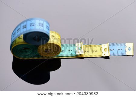 Length And Tailoring. Measuring Tape Rolls Placed On Each Other