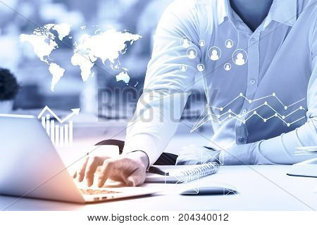 Male hand using laptop with abstract business hologram placed on white office desktop with supplies and other items. Blurry background. Accounting concept