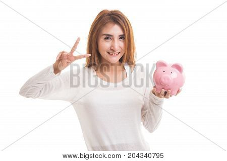 Asian Woman Show Victory Sign With Pig Coin Bank.