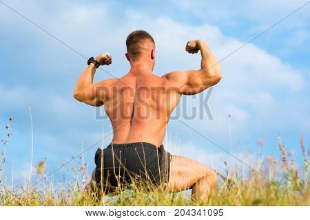 Bodybuilder Flexing Back Muscles Outdoors