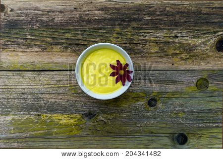 Mayonnaise sauce in a bowl on wooden background.