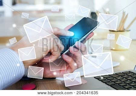 Side view of male hands using smartphone with emails at modern workplace. E-mail network concept