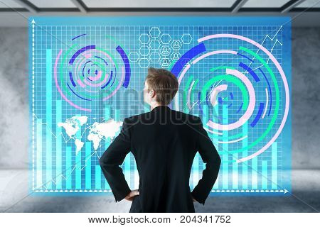 Back view of young businessman in concrete interior looking at abstract business screen. Finance and innovation concept. 3D Rendering