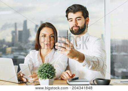 Attractive Businessman And Woman Using Smartphone