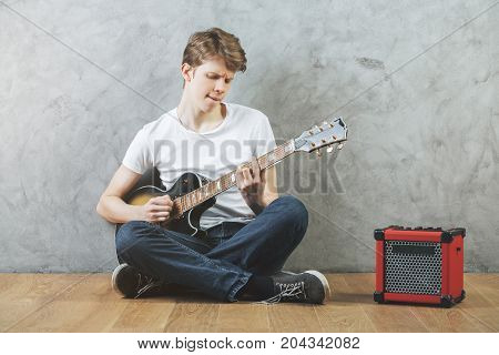 Portrait of european man sitting on wooden floor with amplifier and guitar in hands. Concrete wall background. Music concert hobby rehearsal lifestyle concept