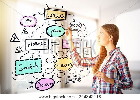 Thoughtful young woman drawing creative business sketch on blurry office interior background. Marketing concept