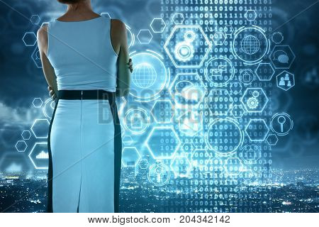 Back view of young businesswoman standing on rooftop with abstract business charts and diagrams on city and sky background. Future and technology concept. Double exposure