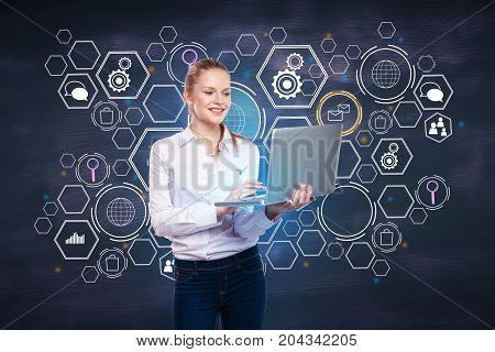 Cheerful young woman using laptop with digital business hologram on chalkboard wall background. Innovation concept