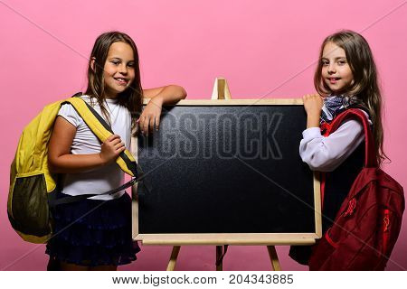 Schoolgirls Next To Chalkboard On Pink Background