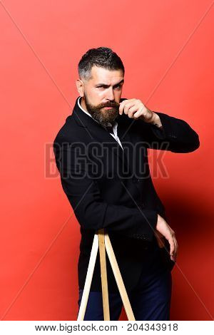 Photography And Profession Concept. Macho Man Leans On Photo Tripod