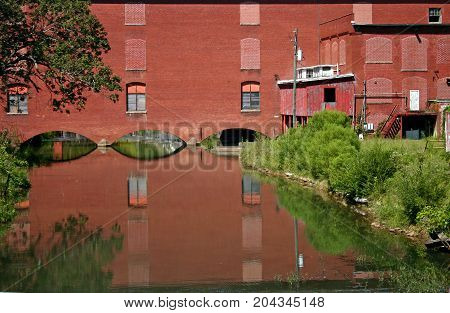 a red brick factory is reflected in calm water