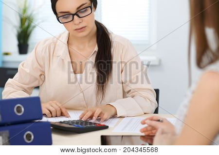Two female accountants counting on calculator income for tax form completion. Internal Revenue Service inspector checking financial document. Planning budget, audit  concept.