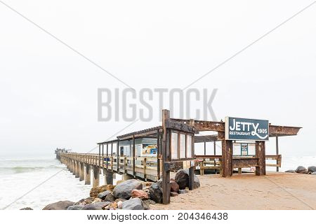SWAKOPMUND NAMIBIA - JUNE 30 2017: The historic jetty with a restaurant on its far end in Swakopmund in the Namib Desert on the Atlantic Coast of Namibia