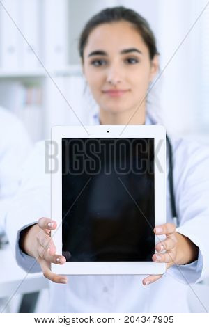 Young female doctor holding touch pad or tablet with copy space. Advertising in medicine.