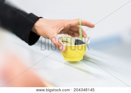 Close-up hand of buyer with two balls of different soft ice cream. Delicious cooling portion on hot day for fun. Real scene in store on light background. Copy space, for background
