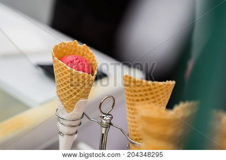 Close-up of fruit, natural, strawberry Ice-cream red color in waffle cone. Selective focus. Real scene in the store. Selective focus. Concept of delicacy, sweets, lifestyle, summer, heat