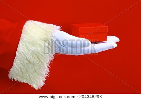 Santa Claus hand presenting your christmas text or product over red background with copy space.