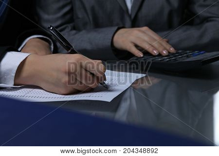 Two female accountants checking financial statement or counting by calculator income for tax form, hands close-up and low key lighting. Internal Revenue Service inspector checking financial document. Planning budget and audit concept.