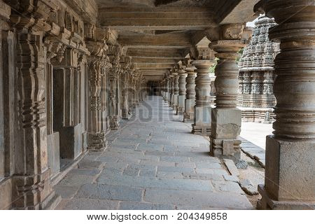 Mysore India - October 27 2013: Landscape shot of beige stone columned corridor along outside wall of Chennakesava Templ in Somanathpur village. Ceilings and row of pillars till the end.