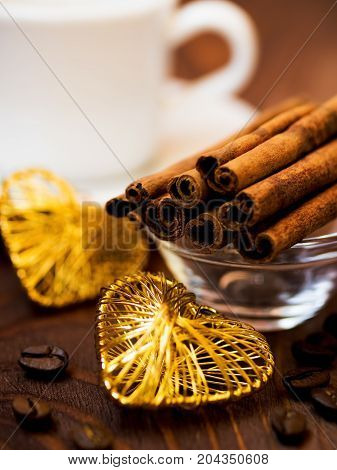 Cup of coffee cinnamon sticks and coffee beans on the table. Saint Valentine's day concept